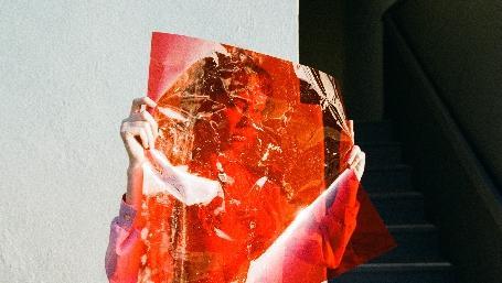 volto di donna dietro ad un foglio trasparente rosso - foto thought per unsplash.com