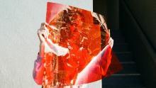donna dietro ad un lucido rosso trasparente (photo by unsplash.com)